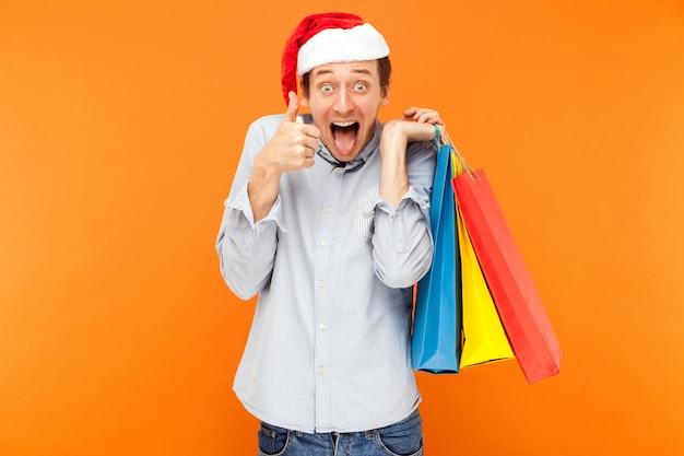 Giovane uomo adulto con cappello natalizio che tiene in mano borse colorate dopo aver fatto shopping pollice in alto e lingua fuori