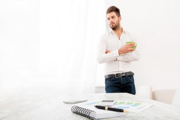 Un giovane uomo adulto a casa a bere caffè.