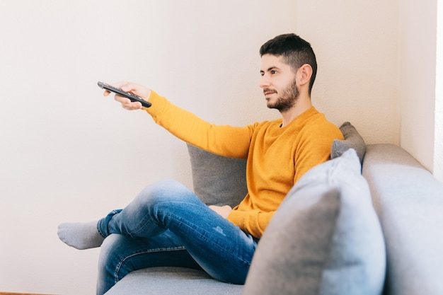 Giovane uomo adulto che guarda un film in televisione a casa. concetto di relax, intrattenimento, video e tecnologia al chiuso.