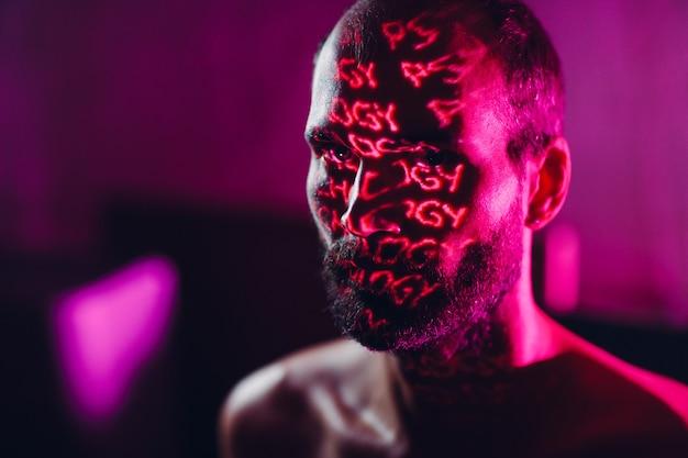 Giovane uomo adulto con la parola psicologia sul viso al buio.