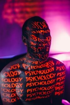 Il giovane adulto con la parola psicologia sul viso grida nel buio.