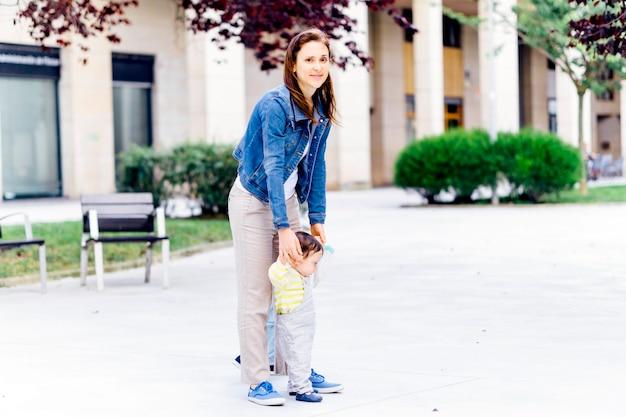 Giovane madre adulta che aiuta il figlio di un anno a muovere i primi passi