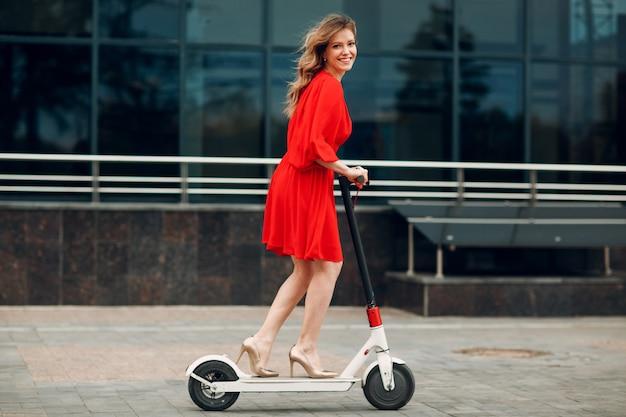Giovane donna adulta perfetta guida scooter elettrico in abito rosso in città