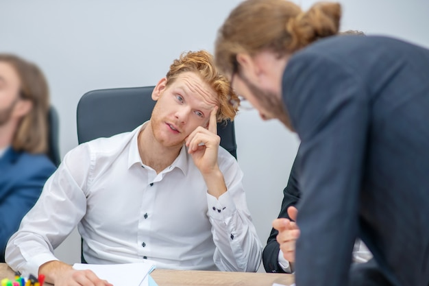 Giovane adulto redhaired uomo attento al tavolo ascoltando il suo collega durante i negoziati in ufficio