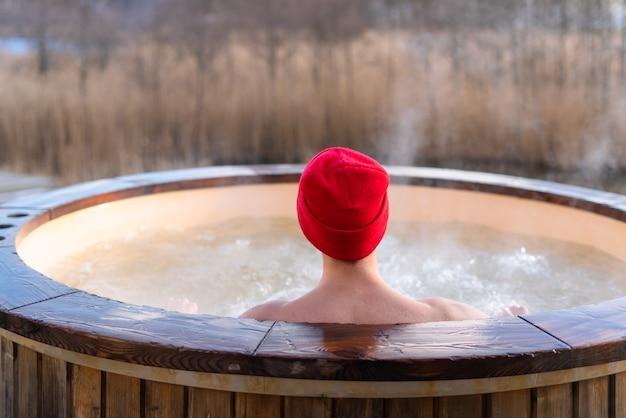 Giovani adulti che si rilassano nella vasca idromassaggio in legno all'esterno e guardano la natura. persona che si gode una piscina calda e fumante in una giornata di sole, trattamento termale privato