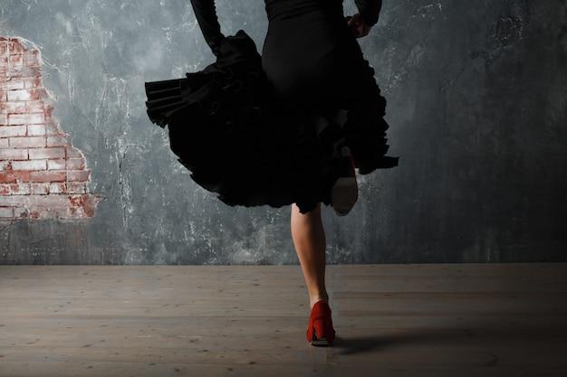 Giovane donna spagnola adulta che balla il flamenco su sfondo grigio vintage studio