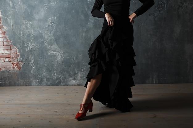 Giovane donna spagnola adulta danza flamenco su sfondo grigio vintage