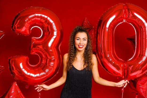 Una giovane donna adulta su uno sfondo di palloncini rossi a forma di numero trenta modello brunett...