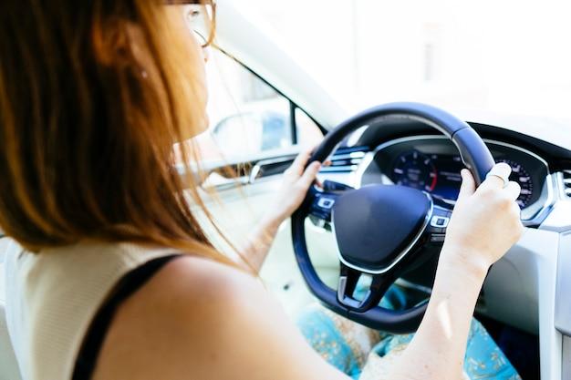 Giovane donna adulta alla guida di un'auto moderna