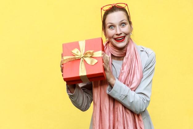 Giovane donna adulta che tiene in mano una confezione regalo e guarda la macchina fotografica e sorride a trentadue denti. su sfondo giallo. foto in studio