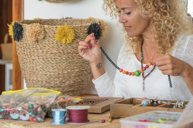 La giovane donna adulta produce gioielli di perline a casa al tavolo