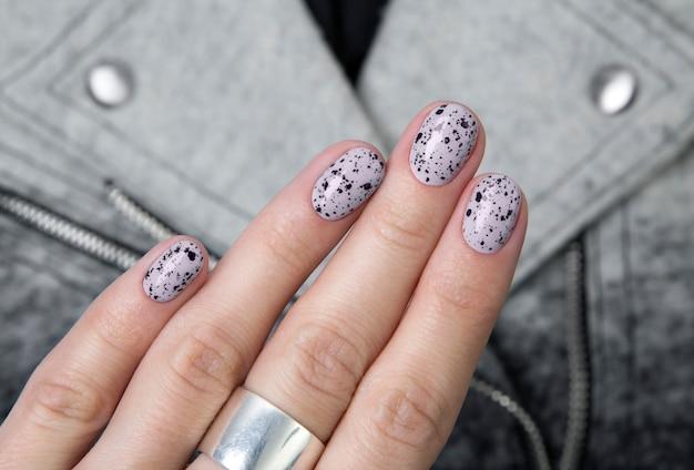 Le mani della giovane donna adulta con i chiodi alla moda nudi rosa sulla tavola di cemento grigia