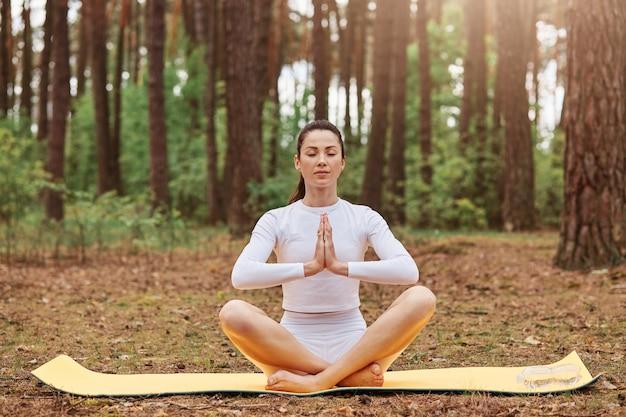 Giovane donna adulta seduta a terra su karemat nella posa del loto, tenendo i palmi uniti, posando con gli occhi chiusi, rilassandosi e meditando all'aria aperta nella foresta, yoga sulla natura.