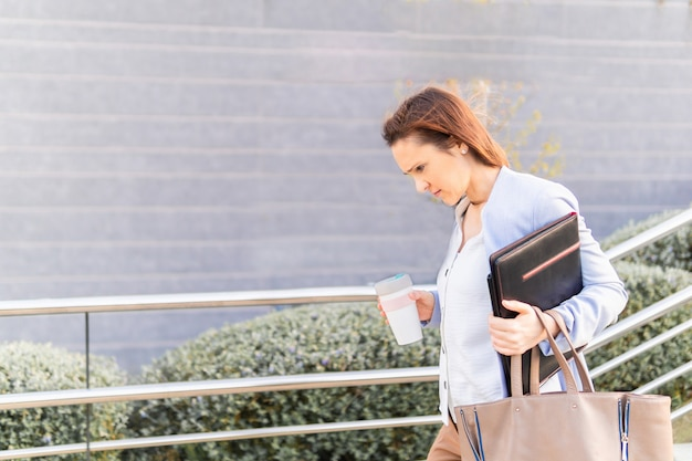 Giovane donna adulta sorridente bella imprenditrice lasciando lavorare con caffè per andare laptop e cartella. concetto di donna d'affari di successo
