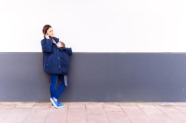 Giovane donna adulta che parla sullo smartphone portando il suo bambino appoggiato a un muro grigio e bianco con un gesto serio che riceve cattive notizie