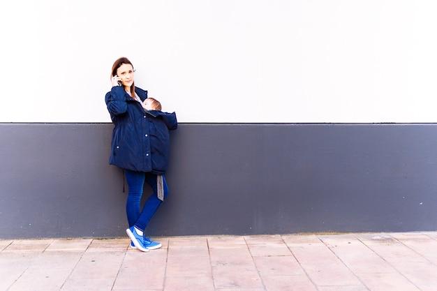 Giovane donna adulta che parla sullo smartphone portando il suo bambino appoggiato su un muro grigio e bianco con sorridente che riceve guardando la parte anteriore