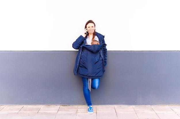 Giovane donna adulta che parla sullo smartphone portando il suo bambino appoggiato su un muro grigio e bianco
