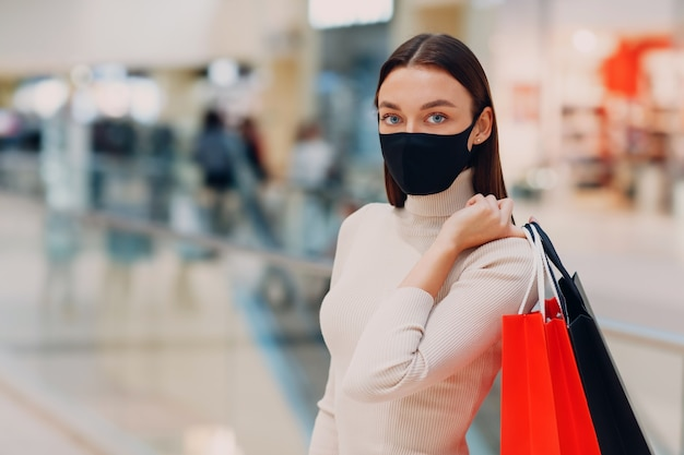 Giovane donna adulta vestita di nero maschera protettiva medica che trasportano i sacchetti della spesa di carta in mani al centro commerciale. black friday e covid-19 new normal.