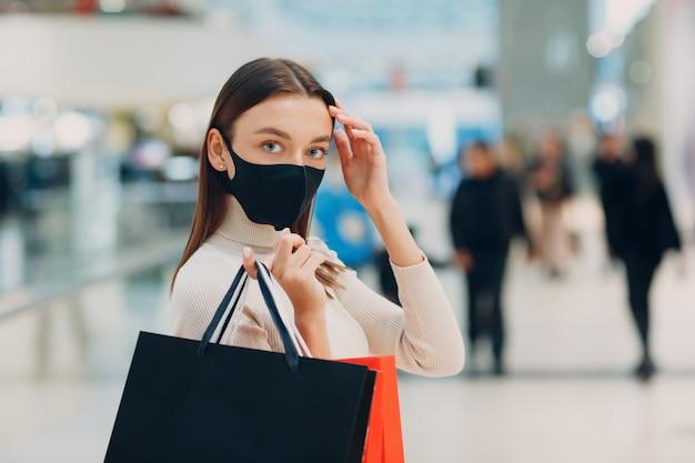 Giovane donna adulta che indossa la maschera protettiva medica che trasportano i sacchetti della spesa di carta in mani al centro commerciale. black friday e covid-19 new normal.
