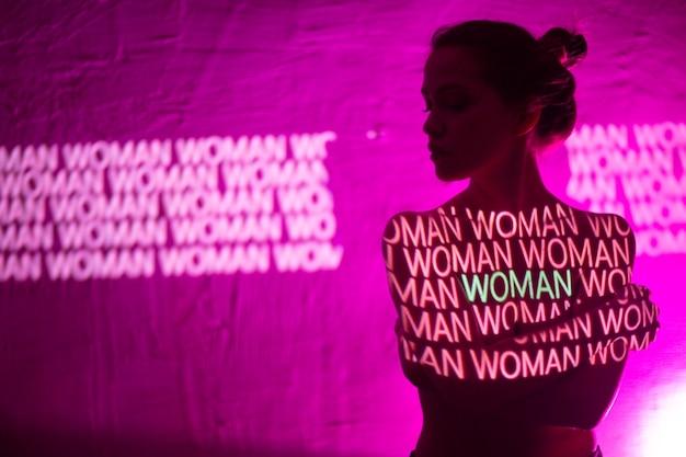 Giovane donna adulta con la parola donna sul suo corpo.