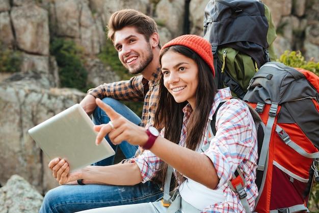 Coppia giovane avventuriero con tavoletta vicino al canyon
