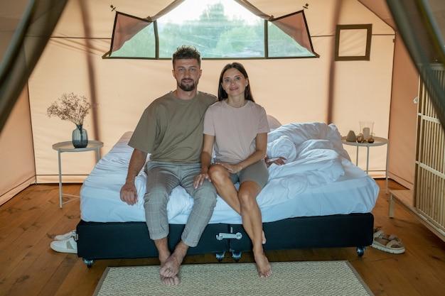 Giovane coppia affettuosa in abbigliamento casual seduto sul letto matrimoniale