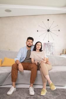 Giovane coppia affettuosa che guarda film in tv nel soggiorno