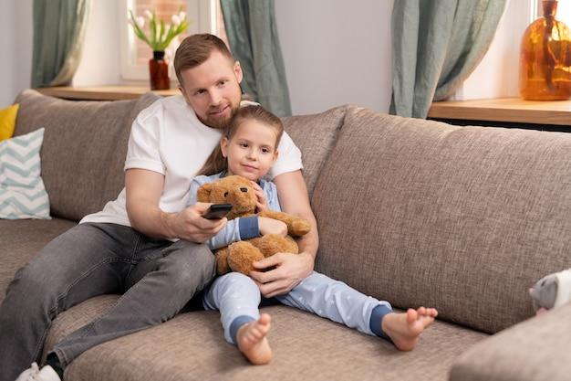 Giovane uomo affettuoso con telecomando che abbraccia la sua adorabile piccola figlia con orsacchiotto mentre entrambi si rilassano sul divano di casa