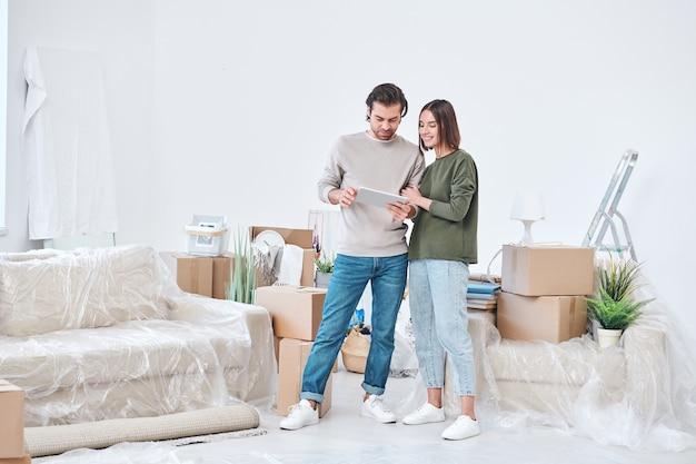 Giovane uomo e donna affettuosi in abbigliamento casual guardando il display della tavoletta digitale e discutendo idee online per il loro nuovo appartamento o casa
