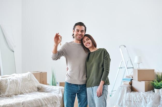 Giovane donna affettuosa che abbraccia il marito con la chiave della loro nuova casa o appartamento mentre entrambi sono in piedi nella stanza con roba disimballata