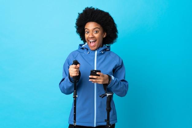 Giovane americano africano con zaino e bastoncini da trekking sulla parete blu sorpreso e l'invio di un messaggio