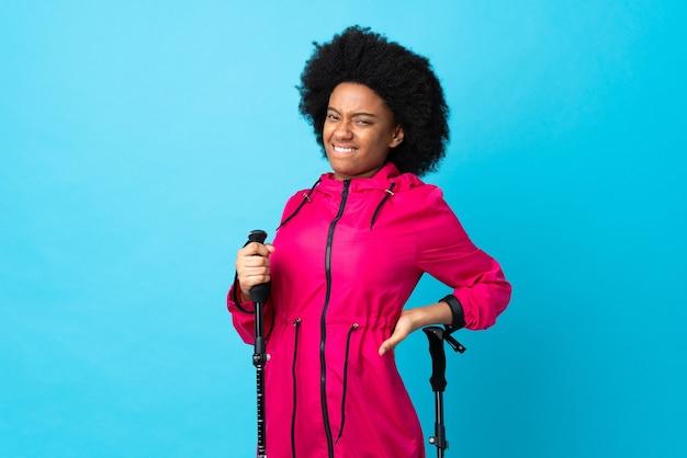 Young africa american con zaino e bastoncini da trekking isolati su sfondo blu che soffrono di mal di schiena per aver fatto uno sforzo