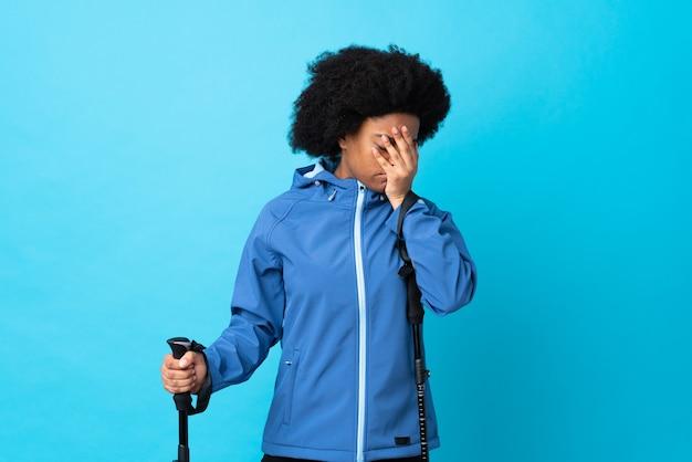 Young africa american con zaino e bastoncini da trekking isolati su sfondo blu con espressione stanca e malata