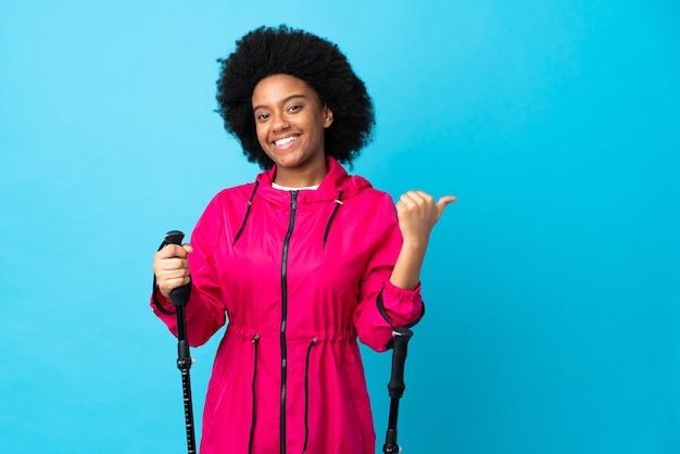 Young africa american con zaino e bastoncini da trekking isolati su blu che punta di lato per presentare un prodotto