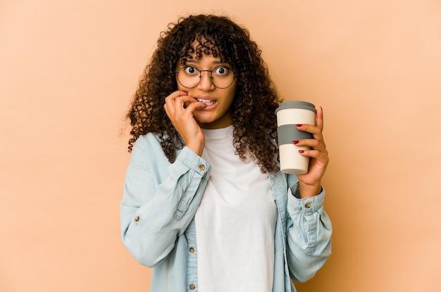 Giovane donna afroamericana afro che tiene un caffè da asporto che morde le unghie, nervosa e molto ansiosa.