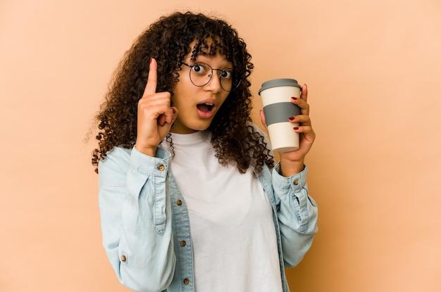 Giovane donna afroamericana afro che tiene un caffè da asporto che ha un'idea, concetto di ispirazione.