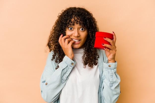 Giovane donna afroamericana afro che tiene un regalo di san valentino con le unghie mordaci, nervose e molto ansiose.