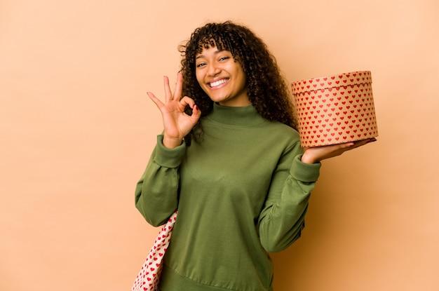 Giovane donna afroamericana afro che tiene un regalo di san valentino allegro e fiducioso che mostra gesto giusto.