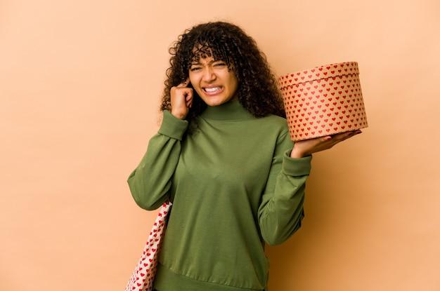 Giovane donna afroamericana afro che tiene un regalo di san valentino che copre le orecchie con le mani.