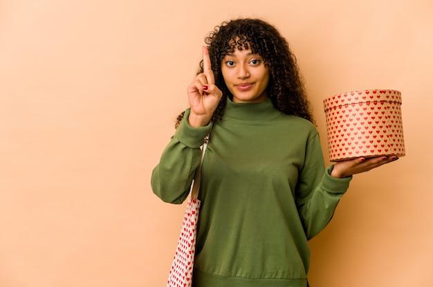 Giovane donna afroamericana afro che tiene un regalo di san valentino che mostra il numero uno con il dito.