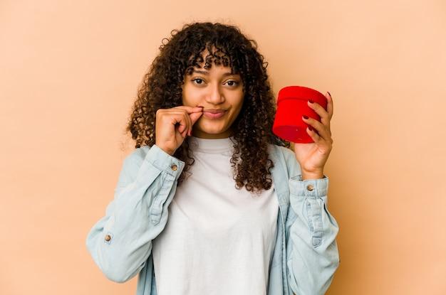 Giovane donna afroamericana afro che tiene un regalo di san valentino con le dita sulle labbra mantenendo un segreto.