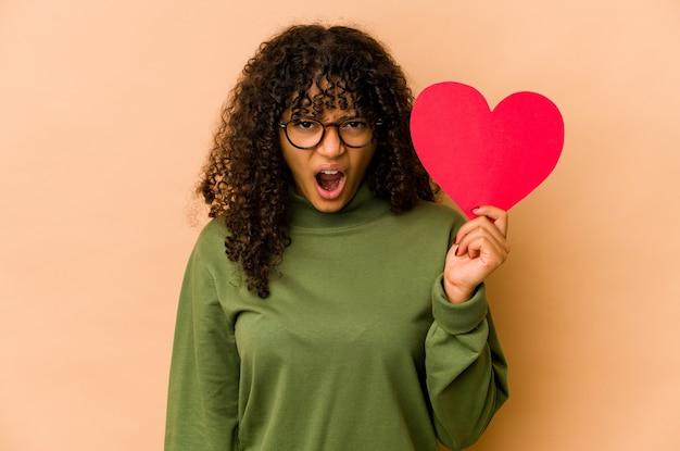 Giovane donna afroamericana afro che tiene un cuore di san valentino urlando molto arrabbiato e aggressivo.