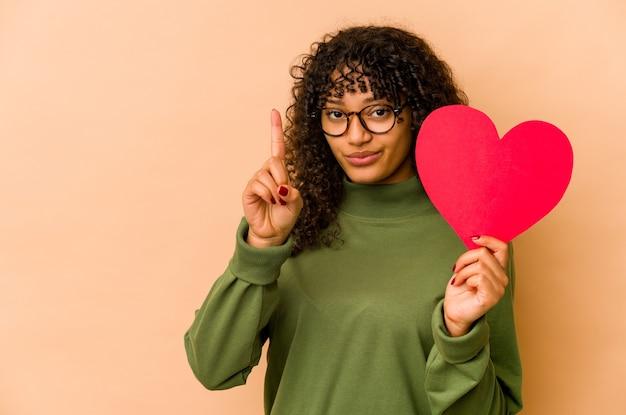Giovane donna afroamericana afro che tiene un cuore di san valentino che mostra il numero uno con il dito.