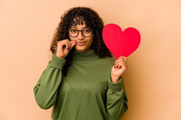 Giovane donna afroamericana afro che tiene un cuore di san valentino con le dita sulle labbra mantenendo un segreto.