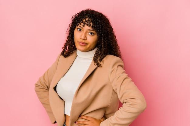 La giovane donna afroamericana afro isolata confusa, si sente dubbiosa e insicura.