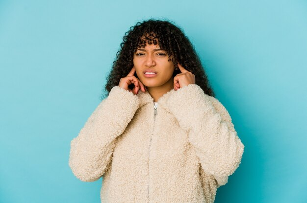 Giovane donna afroamericana afro isolata che copre le orecchie con le dita, stressata e disperata da un ambiente rumoroso.