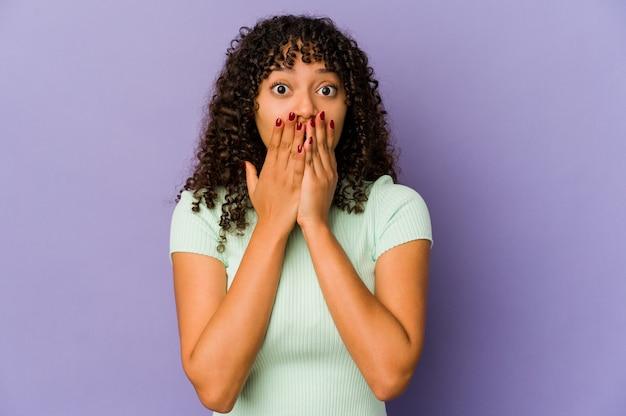 Giovane donna afroamericana afro isolata scioccata, che copre la bocca con le mani, ansiosa di scoprire qualcosa di nuovo.