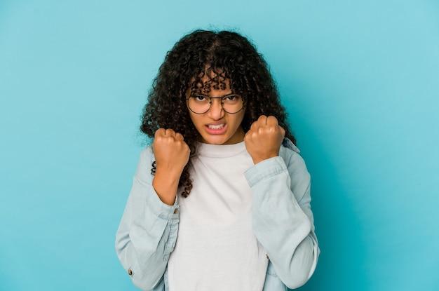 Giovane donna afroamericana afro isolata che mostra pugno, espressione facciale aggressiva.