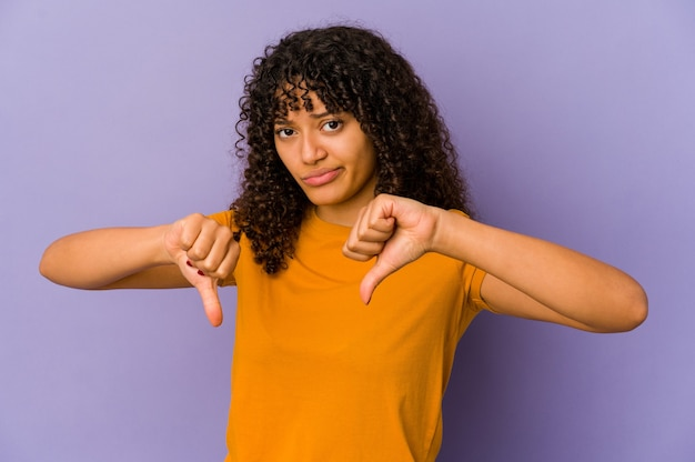 Giovane donna afroamericana afro isolata che mostra pollice verso il basso, concetto di delusione.