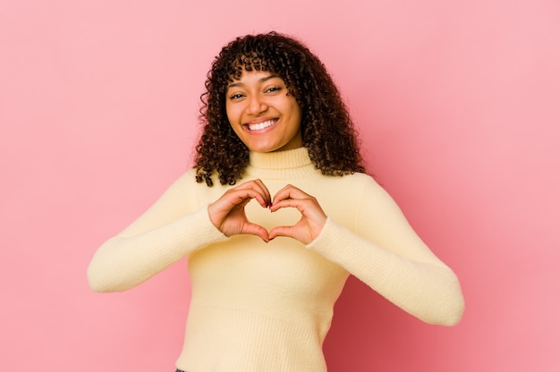 Giovane donna afroamericana afro isolata sorridente e mostrando una forma di cuore con le mani.